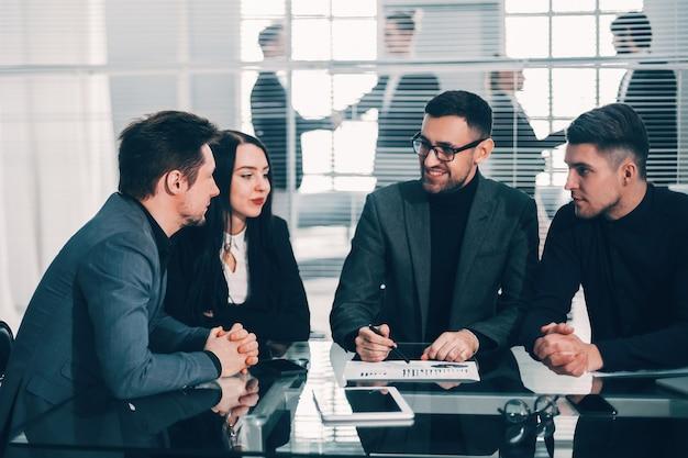 Ekspert analizujący wykresy finansowe na spotkaniu z zespołem biznesowym