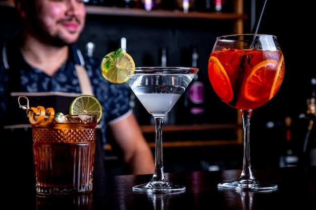 Ekspert barman robi koktajl w klubie nocnym. profesjonalny barman w pracy w barze wlewając słodki napój do szklanki na imprezie w klubie nocnym. barman ozdabia koktajl.