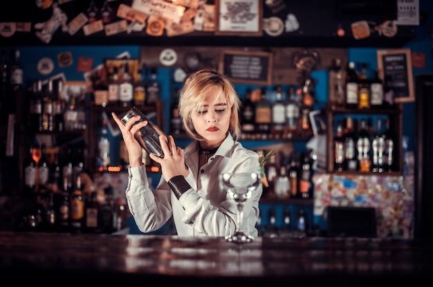 Ekspert barman wlewając świeży napój alkoholowy do szklanek w barze koktajlowym