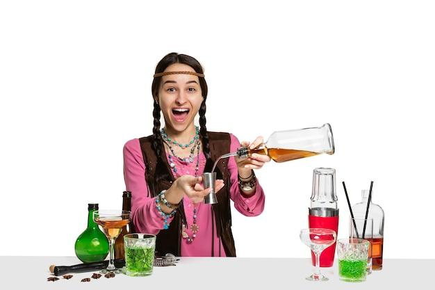 Ekspert kobieta barman robi koktajl w studio na białym tle. międzynarodowy dzień barmana, bar, alkohol, restauracja, impreza, pub, życie nocne, koktajl, koncepcja klubu nocnego