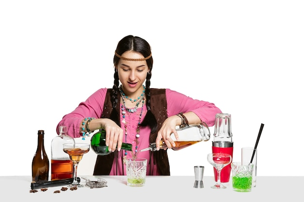 Ekspert kobieta barman robi koktajl w studio na białym tle na białej ścianie
