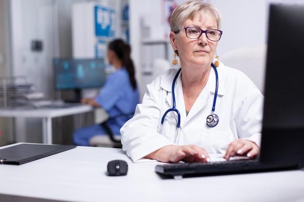 Ekspert kobieta lekarz pracuje przy komputerze, wprowadzając dane z kartoteki pacjenta. kobieta lekarz w białym fartuchu i stetoskop siedzi w gabinecie szpitalnym, pisząc na klawiaturze komputera z pielęgniarką w tle