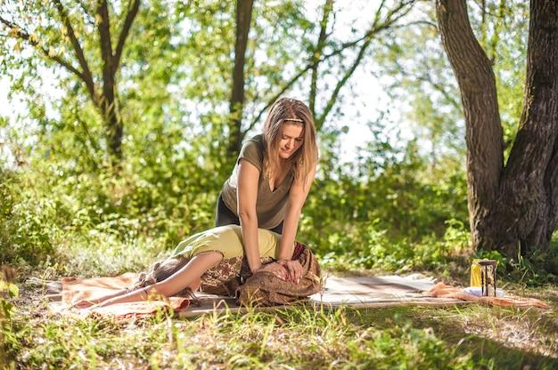 Ekspert masażu demonstruje na leśnej trawie orzeźwiające metody masażu.