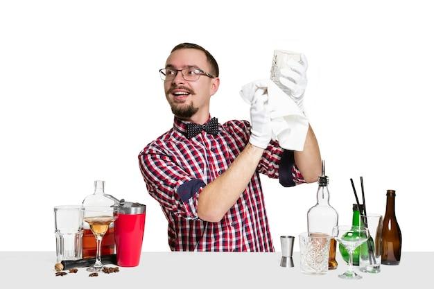Ekspert męski barman robi koktajl na białym tle na białej ścianie. międzynarodowy dzień barmana, bar, alkohol, restauracja, impreza, pub, życie nocne, koktajl, koncept klubu nocnego