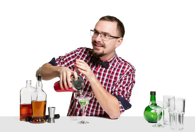 Ekspert męski barman robi koktajl na na białym tle na białej ścianie.