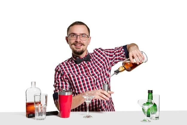 Ekspert mężczyzna barman robi koktajl na na białym tle na białej ścianie. międzynarodowy dzień barmana, bar, alkohol, restauracja, impreza, pub, życie nocne, koktajl, koncepcja klubu nocnego