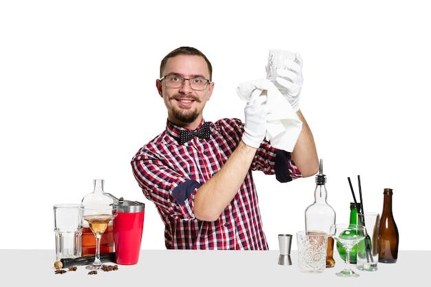 Ekspert mężczyzna barman robi koktajl w studio na białym tle na białej ścianie