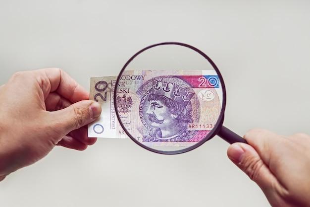 Ekspert z lupą sprawdza podejrzane pieniądze. szukaj znaków wodnych na papierze fałszywych rachunków. lupa, lupa, lupa, lupy, lupa
