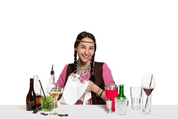 Ekspert żeński barman robi koktajl na na białym tle na białej ścianie.