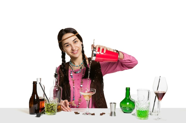 Ekspert żeński barman robi koktajl w studio na białym tle na białej ścianie
