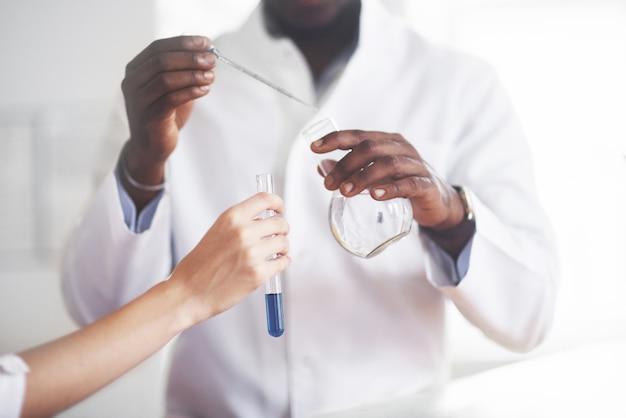 Eksperymenty w laboratorium chemicznym. eksperyment przeprowadzono w laboratorium w przezroczystych kolbach.