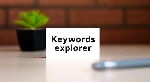 Eksplorator słów kluczowych - tekst koncepcji biznesowej na białej liście i za pomocą pióra i czarny garnek z kwiatem w tyle