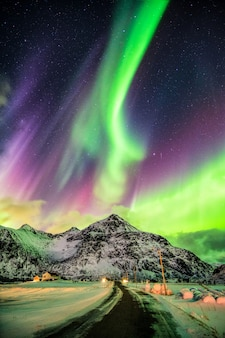 Eksplozja aurora borealis (northern lights) nad górami i wiejską drogą