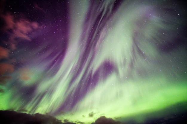 Eksplozja aurora borealis (zorza polarna) z gwiazdami na nocnym niebie na kole podbiegunowym