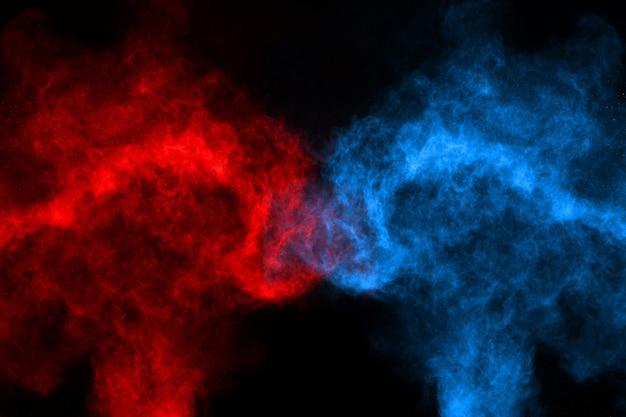Eksplozja niebieskiego i czerwonego proszku na czarnym tle