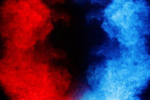 Eksplozja proszku w kolorze niebieskim i czerwonym na czarnym tle