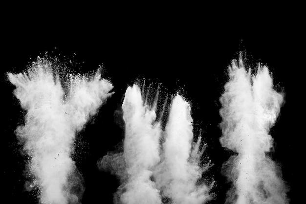 Eksplozja talku biały proszek na czarnym tle. rozpryskują się białe cząsteczki pyłu.