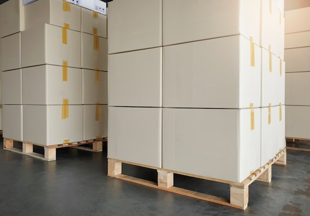 Eksport ładunków, spedycja, stos kartonów na paletach drewnianych. magazyn produkcyjny i transport spedycyjny.