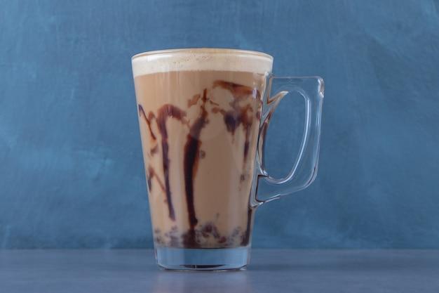 Ekspozycja czekoladowego cappuccino na niebieskim tle. zdjęcie wysokiej jakości