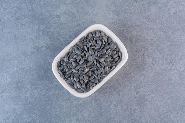 Ekspozycja nieobranych nasion słonecznika na marmurowej powierzchni