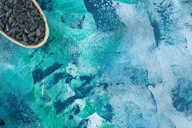 Ekspozycja nieobranych nasion słonecznika na misce, na marmurowym stole.
