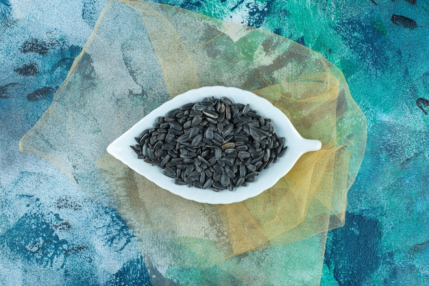 Ekspozycja nieobranych nasion słonecznika na tiulu, na marmurowym stole.