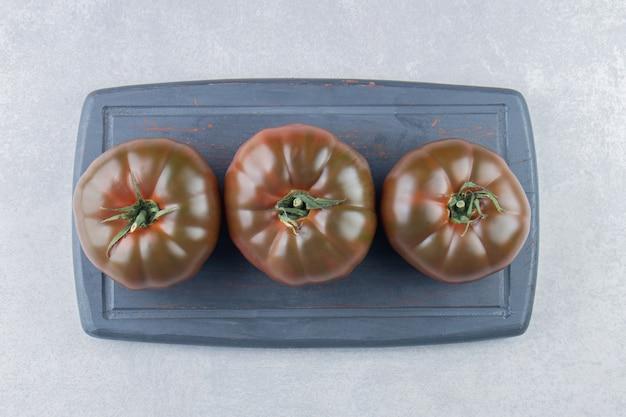 Ekspozycja pomidorów na tacy na marmurowej powierzchni