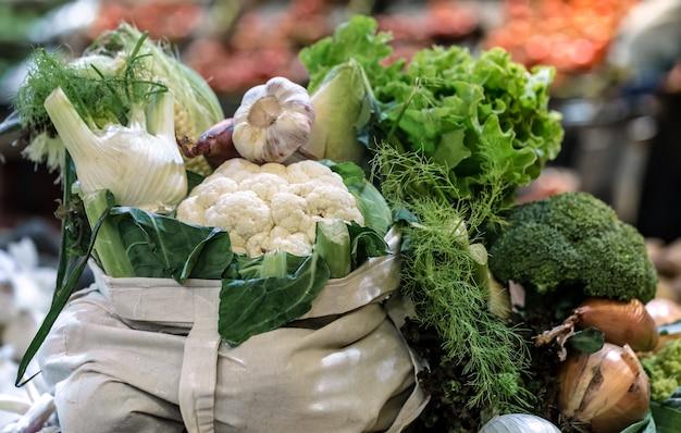 Ekspozycja świeżych dojrzałych brokułów organicznych, sałatki z zieleniną i warzywami w bawełnianej torbie na weekendowym targu
