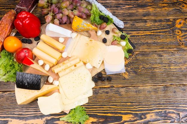 Ekspozytor bufetowy z wyborem różnych serów wyświetlanych na drewnianej desce serów przyozdobionej cebulą koktajlową, oliwkami, jeżynami, winogronami, pomidorem i papryką, widok z góry z copyspace