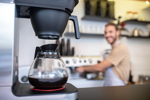 Ekspres do kawy. ekspres do kawy ze szklanym dzbankiem kawy stojący na blacie i człowiek na odległość w kawiarni