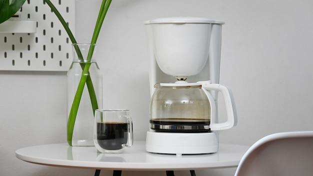 Ekspres do kawy i filiżanka kawy w pokoju biurowym.