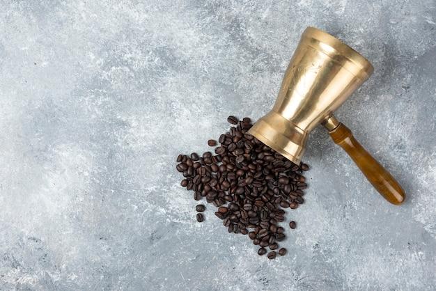 Ekspres do kawy pełen palonych ziaren kawy na marmurowej powierzchni.