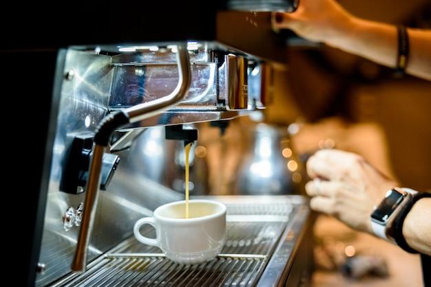 Ekspres do kawy przygotowuje espresso na śniadanie klientów w europejskiej kawiarni.