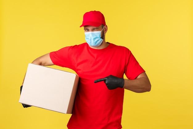 Ekspresowa dostawa podczas pandemii, covid-19, bezpieczna wysyłka, koncepcja zakupów. bezczelny przystojny kurier przyniesie paczkę, mruga i wskazuje pudełko, załóż maskę medyczną chroniącą przed rozprzestrzenianiem się koronawirusa.