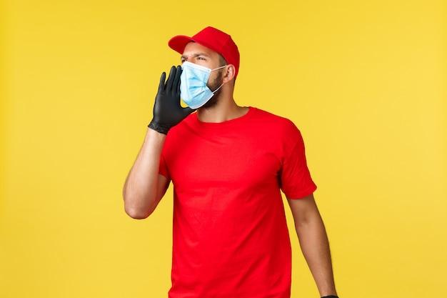 Ekspresowa dostawa podczas pandemii, covid-19, bezpieczna wysyłka, koncepcja zakupów. młody zajęty kurier w czerwonym mundurze, masce medycznej i rękawiczkach, krzyczy na współpracownika, wzywając pomoc ręką przy ustach