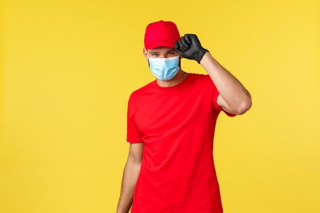 Ekspresowa dostawa podczas pandemii, covid-19, bezpieczna wysyłka, koncepcja zakupów online. charyzmatyczny kurier w czerwonej jednolitej czapce i koszulce, masce medycznej, pozdrawiając klienta, przynieś zamówienie na wyciągnięcie ręki