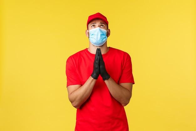 Ekspresowa dostawa podczas pandemii, covid-19, bezpieczna wysyłka, koncepcja zakupów online. kurier z nadzieją, błagający boga o zakończenie infekcji koronawirusem, ściśnięcie rąk w modlitwie, patrzenie w górę, noszenie maseczki na twarz