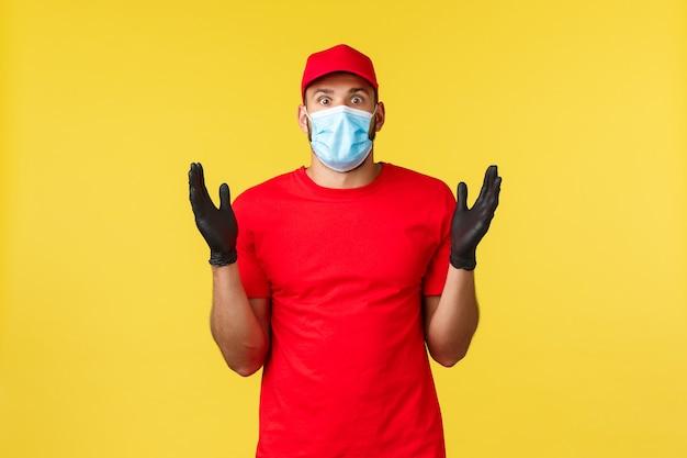 Ekspresowa dostawa podczas pandemii, covid-19, bezpieczna wysyłka, koncepcja zakupów online. pod wrażeniem i zaskoczonym kurierem w czerwonej czapce mundurowej, podkoszulku podnoszącym ręce zdumiony, noszącym maseczkę medyczną