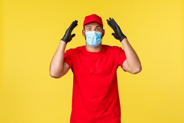 Ekspresowa dostawa podczas pandemii, covid-19, bezpieczna wysyłka, koncepcja zakupów online. podekscytowany i zaskoczony młody kurier znalazł oszałamiające informacje, pokazał boom, założył maskę medyczną