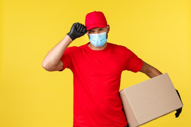 Ekspresowa dostawa podczas pandemii, covid-19, bezpieczna wysyłka, koncepcja zakupów online. poważnie zdeterminowany kurier chroniący paczkę klientów, trzymający pudełko, salutujący z czapką, noszący maskę medyczną i rękawiczki