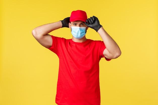 Ekspresowa dostawa podczas pandemii, covid-19, bezpieczna wysyłka, koncepcja zakupów online. poważny przystojny kurier założył mundurową czerwoną czapkę, założył maskę medyczną i rękawiczki, będąc gotowym do dostarczenia zamówienia