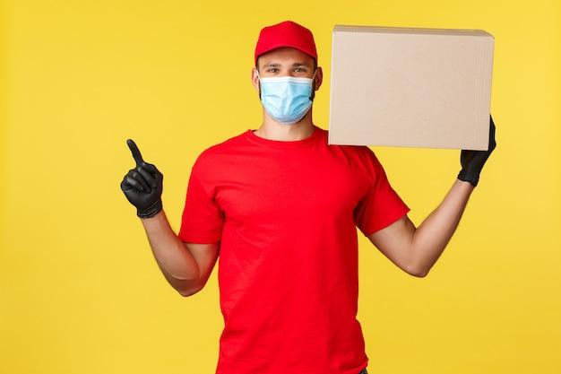 Ekspresowa dostawa podczas pandemii, covid-19, bezpieczna wysyłka, koncepcja zakupów online. przystojny dostawca, kurier trzymający pudełko z paczką i wskazujący lewy górny róg, nosić maskę medyczną