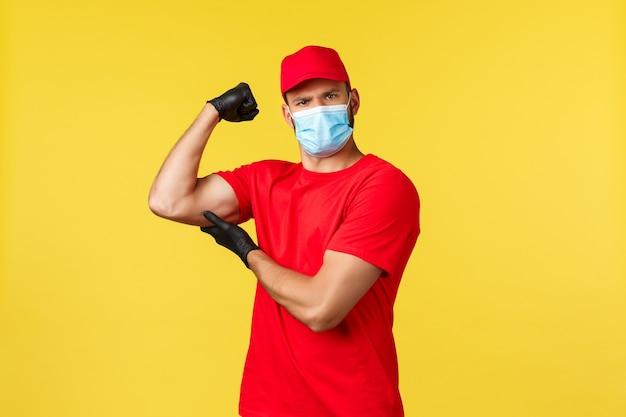 Ekspresowa dostawa podczas pandemii, covid-19, bezpieczna wysyłka, koncepcja zakupów online. silny i zdeterminowany kurier w czerwonym mundurze, masce medycznej i rękawiczkach, zgiętym bicepsie, chwali się mięśniami