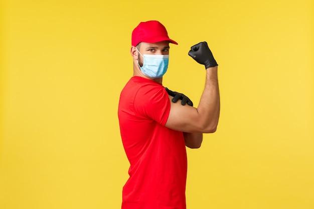 Ekspresowa dostawa podczas pandemii, covid-19, bezpieczna wysyłka, koncepcja zakupów online. silny młody kurier w czerwonej firmie mundurowej i masce medycznej, pokaż mięśnie, zginaj biceps na żółtym tle