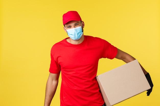 Ekspresowa dostawa podczas pandemii, covid-19, bezpieczna wysyłka, koncepcja zakupów online. szczęśliwy charyzmatyczny kurier dostarcza zamówienie do domu, uśmiechnięty klient, trzymaj pudełko noś maskę medyczną i rękawiczki