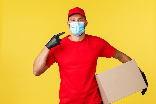 Ekspresowa dostawa podczas pandemii, covid-19, bezpieczna wysyłka, koncepcja zakupów online. uśmiechnięty kurier w czerwonym mundurze, trzymający paczkę, wskazujący na maskę medyczną na twarzy, zabezpiecza klientów przed koronawirusem.
