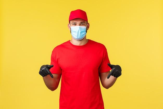 Ekspresowa dostawa podczas pandemii, covid-19, bezpieczna wysyłka, koncepcja zakupów online. uśmiechnięty przyjacielski kurier, dostawca w jednolitej czerwonej czapce i koszulce, masce medycznej, skierowanym w dół