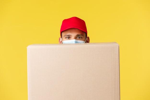 Ekspresowa dostawa podczas pandemii, covid-19, bezpieczna wysyłka, koncepcja zakupów online. zabawny kurier w czerwonej czapce mundurowej, chowający się za pudełkiem, nosić maskę medyczną, żółte tło