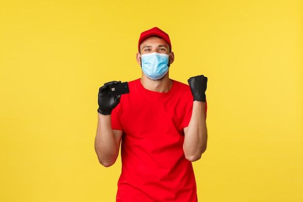Ekspresowa dostawa podczas pandemii, covid-19, bezpieczna wysyłka, koncepcja zakupów online. zadowolony, szczęśliwy kurier w masce medycznej i rękawiczkach, w firmowym czerwonym mundurze, śpiewający, mówiąc tak, pokazując kartę kredytową.