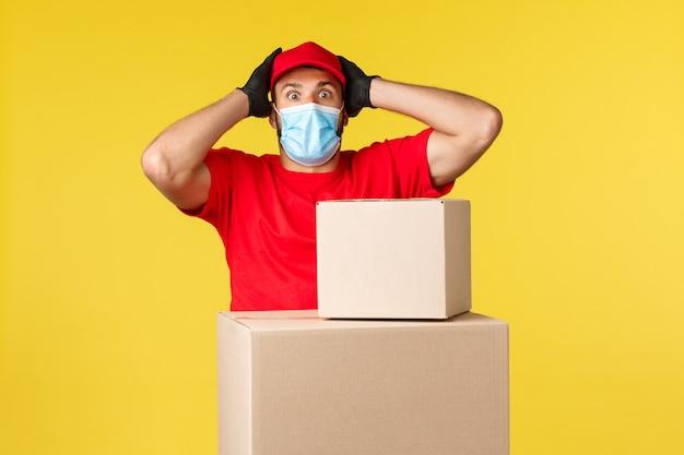 Ekspresowa dostawa podczas pandemii, covid-19, bezpieczna wysyłka, koncepcja zakupów online. zakłopotany i zdenerwowany, spanikowany kurier stojący przy pudłach z paczkami, łapiący oddech, noszący maskę medyczną.